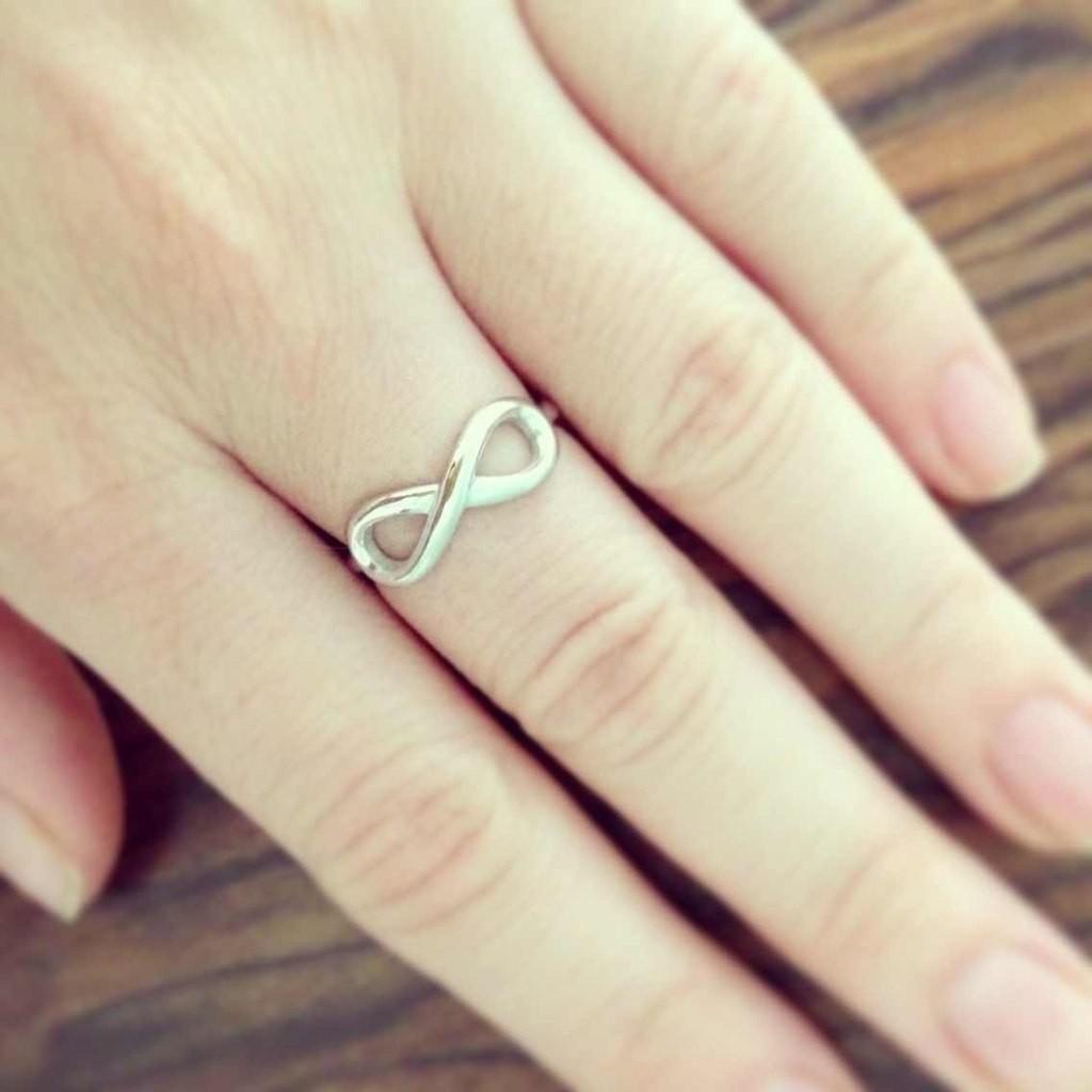 кольцо со знаком бесконечности на пальце
